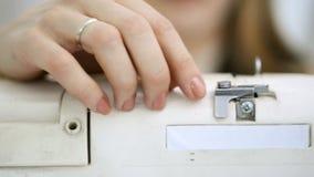 Close-up die handen schieten die roze draad in naaimachine zetten stock videobeelden
