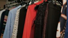 Close-up die rek met hangers met verschillende kleurrijke kleren schieten stock videobeelden