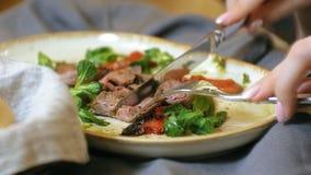 Close-up die schieten: een smakelijke vleesschotel op een plaat, het rundvlees van het rundvleesbraadstuk met paprika's en groene stock videobeelden