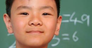 Close-up die van Aziatische schooljongen zich tegen bord in een klaslokaal op school 4k bevinden stock videobeelden