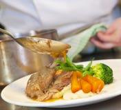 Close-up die van chef-kok hete saus op zijn schotel giet Royalty-vrije Stock Foto