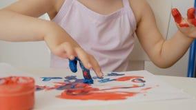 Close-up die van de hand van een klein meisje, op papier met heldere kleuren trekken, die haar vingers in blikken van verf onderd stock video