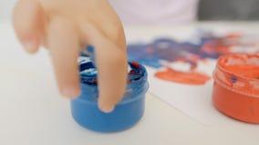 Close-up die van de hand van een klein meisje, op papier met heldere kleuren trekken, die haar vingers in blikken van verf onderd stock videobeelden