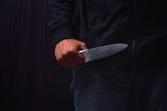 Close-up die van een jonge mensenhand, een mes houden, ongeveer aan aanval, o stock fotografie