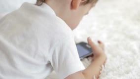 Close-up die van een kind die op de laag liggen, met een smartphone spelen Vage cameranadruk stock videobeelden