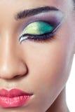 Close-up die van een vrouwelijk gezicht met kleurrijke make-up is ontsproten Stock Foto's