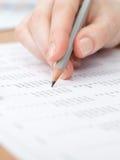 Close-up die van hand is ontsproten die in het document schrijft Stock Foto