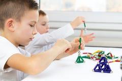Close-up die van jonge geitjes raadsspel spelen terwijl thuis het zitten bij de lijst, magnetische stokken en ballen voor kindont stock foto's