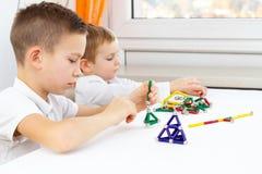 Close-up die van jonge geitjes raadsspel spelen terwijl thuis het zitten bij de lijst, veel kleurrijke magneten voor kindontwikke royalty-vrije stock foto's