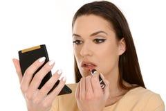 Close-up die van jonge vrouw die lippenstift toepassen, kleine spiegel houden royalty-vrije stock afbeelding