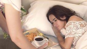Close-up die van jonge vrouw in slaap en haar tedere echtgenoot die aan haar met ontbijt komen liggen stock video