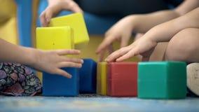 Close-up die van kind` s handen met kleurrijke plastic bakstenen spelen stock footage