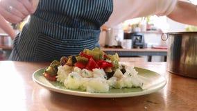 Close-up die van kok fijngestampte die aardappels dienen met kruiden in witte plaat worden voorbereid stock video