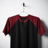 Close-up die van lege katoenen t-shirt, zwarte en rode kleuren in centrum lege concrete muur hangen Ontruim etiketmodel met stock foto's