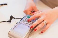 Close-up die van meisjes` s handen die de SPELDcode ingaan, voor de aankoop betalen die magnetische kaart beleggen royalty-vrije stock fotografie