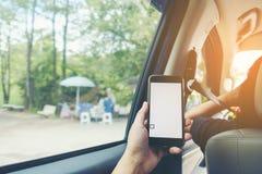 Close-up die van mensen` s handen smartphone in het autobinnenland houden, Stock Foto