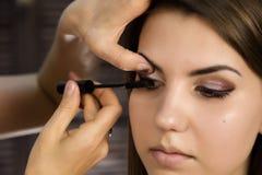 Close-up die van professionele grimeur eyeliner op ooglid toepassen De stilist doet goedmaakt wijfje door eyeliner royalty-vrije stock afbeeldingen