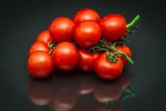 Close-up die van rijpe rode wijnstoktomaten als druiven liggen stock afbeelding