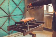 Close-up die van spuitpistool verf over hout krijgen Jonge schilder die, Mens die beschermende handschoenen gebruiken die houten  stock foto