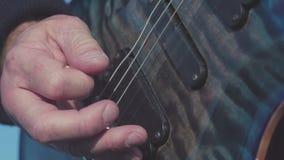 Close-up die van vingers op basgitaar spelen voorraad De basgitaar van gitaristspelen solo in openlucht in daglicht Close-up van stock footage