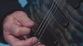 Close-up die van vingers op basgitaar spelen voorraad De basgitaar van gitaristspelen solo in openlucht in daglicht Close-up van stock video