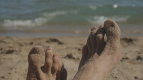 Close-up die van voeten van de Kaukasische mens op zandig strand dichtbij het overzees liggen stock footage