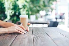 Close-up die van vrouwelijke handen latte houden Close-up van vrouwelijke handen royalty-vrije stock foto's