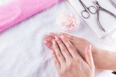 Close-up die van vrouwelijke handen met Franse manicure op een handdoek wordt geschoten, manicurereeks stock foto