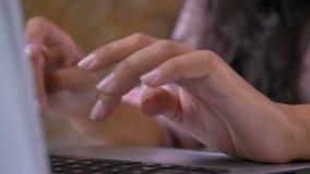 Close-up die van vrouwelijke handen die op een toetsenbord typen, aan laptop werken stock video