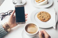 Close-up die van vrouwen` s handen celtelefoon houden terwijl het drinken van koffie en het eten van dessert - haverkoekje in kof Stock Afbeelding