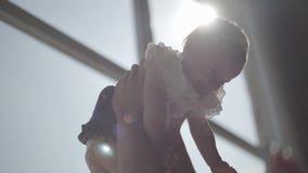 Close-up die van vrouwenhanden haar glimlachend babymeisje omhoog voor groot venster opheffen De moeder die met haar kind spelen  stock video