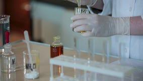 Close-up die van wetenschapper wordt geschoten die rode vloeistof druipen in reageerbuis Het gieten van de vloeistof in de buis v stock footage