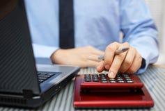Close-up die van zakenman aan calculator en laptop werkt stock afbeelding
