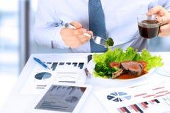 Close-up die van zakenman die aan marketing strategie tijdens bedrijfslunch werken, sappig clublapje vlees eten stock afbeeldingen