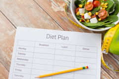 Close up of diet plan and food on table Royalty Free Stock Images