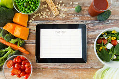 Close up of diet plan on tablet pc and vegetables Royalty Free Stock Photo