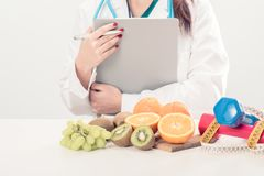 Close up of a dietitian doctor. Writing a diet list on a desk with fruits Royalty Free Stock Photos