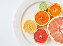 Close up of different citrus fruits - Myers lemon, lime, mandarin, grapefruit and pomelo. Close up of different citrus fruits on a white plate - Myers lemon stock image
