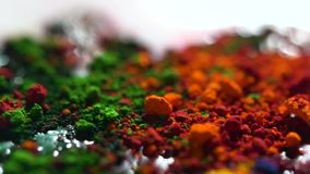 Close up of different color dry inks, art concept. Bright, iridescent background with orange, green, and yellow powder. Close up of different color dry inks stock video