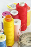 Close up of different colors of thread and meter. Macro of thread in different colors. Focus on the needle with orange thread and meter Royalty Free Stock Photo