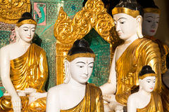 Close up of different sized golden Buddhas Stock Photo