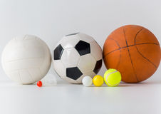 Close up of different sports balls and shuttlecock. Sport, fitness, game, sports equipment and objects concept - close up of different sports balls and Stock Photography