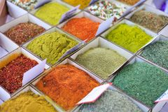 Close-up of different types of colored oriental spices and seasonings on market in square forms with price tags royalty free stock image