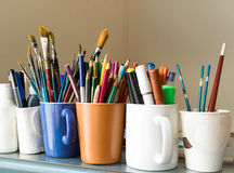 Close up of different used paint brushes, sharpened colored pencils, pens, and markers Royalty Free Stock Photography