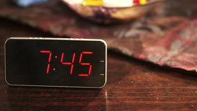 Close-up of a digital clock placed on wooden table when the time's passing stock video footage