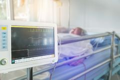 Close up digital vital signs of measuring heart and blood pressure monitor with elderly patient sleep on the bed Stock Photo
