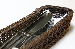 Close up dining utensils in basket on table Royalty Free Stock Photos