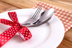 close up dinner setting fork and spoon on plate on wooden backgr Stock Photos