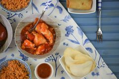 Close up dinner table with cooked oriental food dishes. A flat lay overhead view of a blue wood table and pattern white cloth. With dishes of Chinese or oriental Stock Images