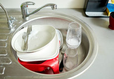 Close up of dirty dishes washing in kitchen sink Stock Photo